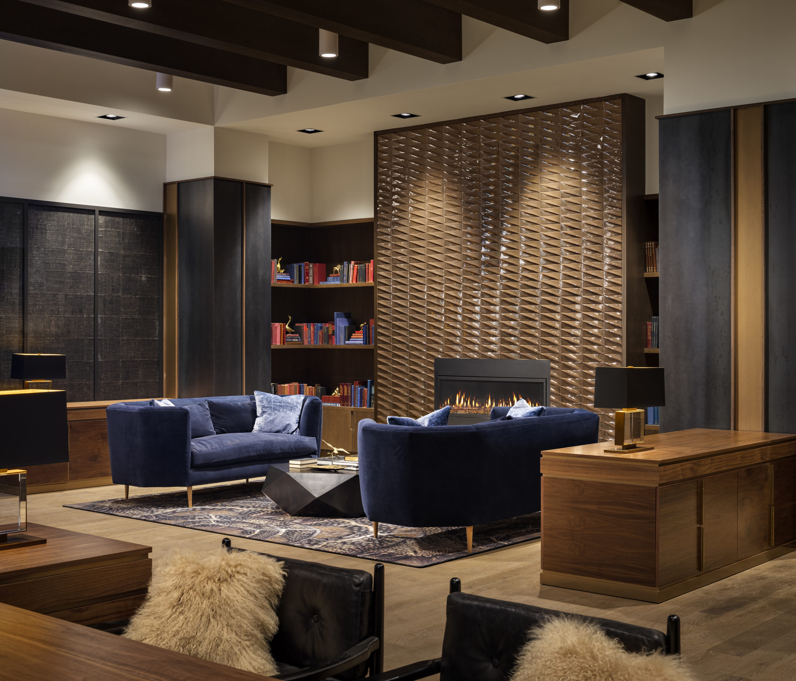 resident library with blue couches and fire place